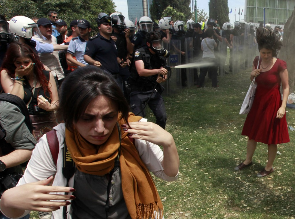 A Turkish riot policeman uses tear gas as people protest against the destruction of trees in a park brought about by a pedestrian project, in Taksim Square in central Istanbul 28 May 2013. REUTERS / Osman Orsal
